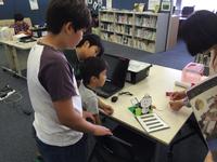 旗を振るリリパンダ君たちと子供たちのロボット教室を訪問!